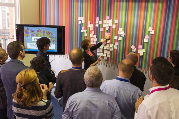 GDS team in a meeting with a speaker placing lots of post-its on a wall.