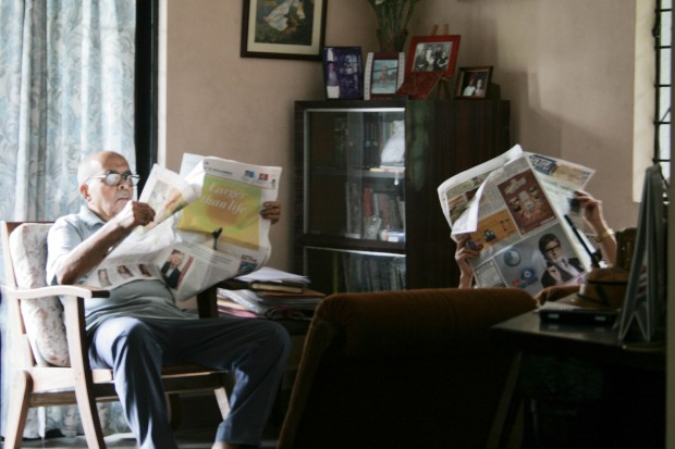 Two people in the room sitting in an arm chair reading newspapers