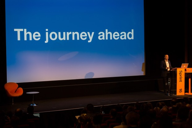Image of the main stage at the Sprint 16 event, with Minister for the Cabinet Office and Paymaster General, standing at the podium and the words 'The journey ahead' on the large screen.