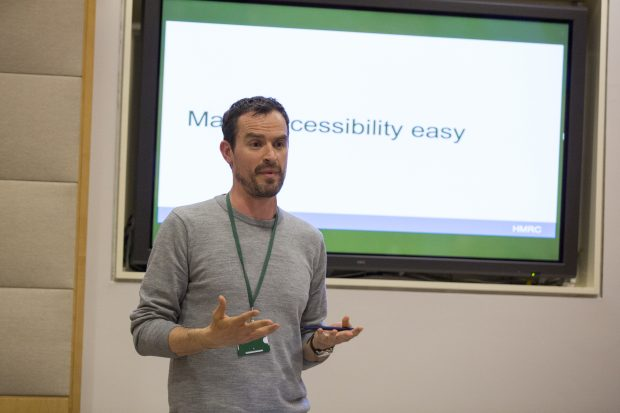 Landscape picture of Alistair Duggin, Head of Accessibility at GDS, standing in front of a screen. On the screen is the text 'Making accessibility easy'